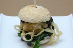 Hamburguesa de calamar y gambas con espinacas, cebolla y alioli negro